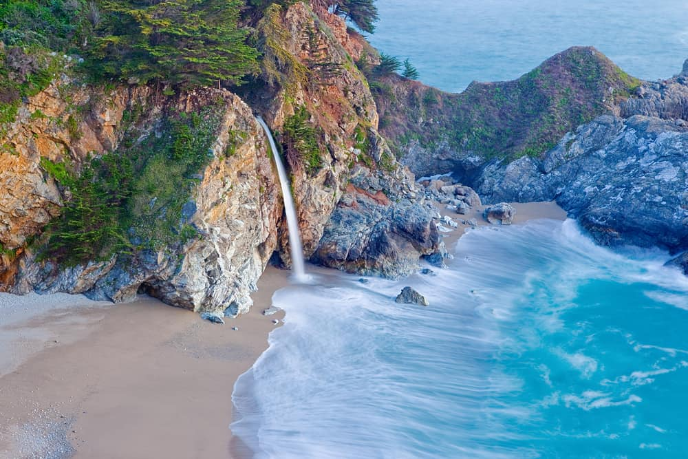 Waterfall emptying out into the beach along the sea in Big Sur