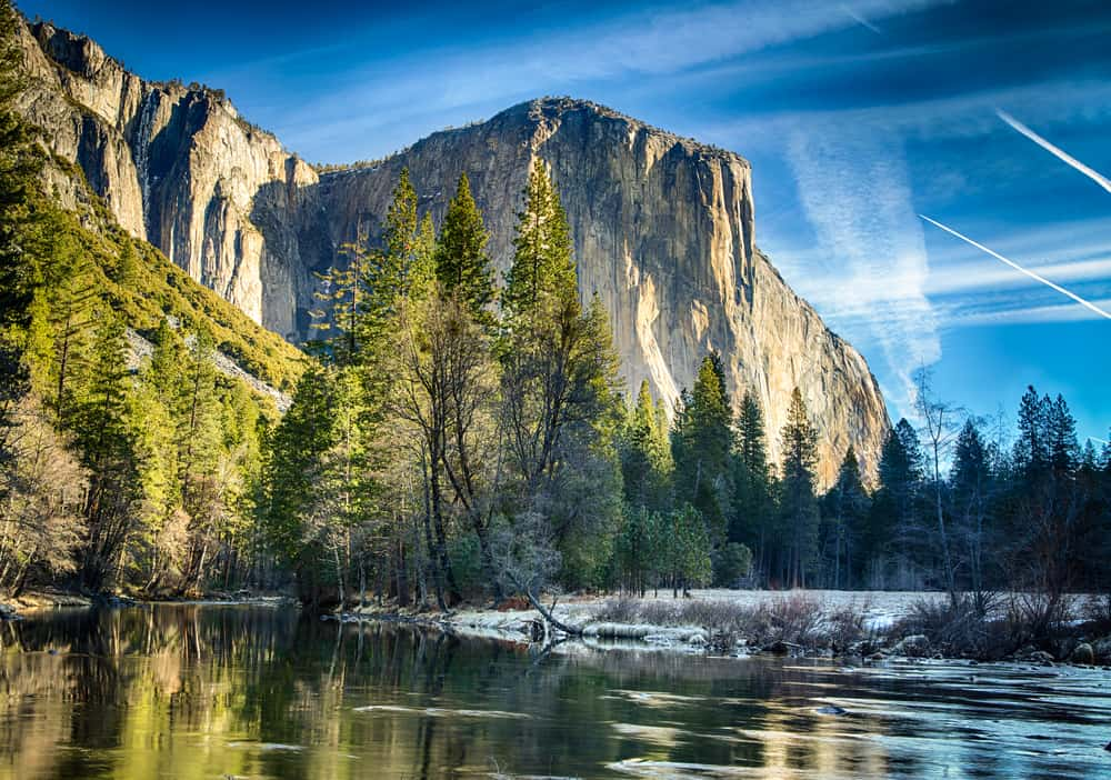 Blue sky with streaky clouds and jet streams with trees and granite cliff faces and a still river reflecting the granite.