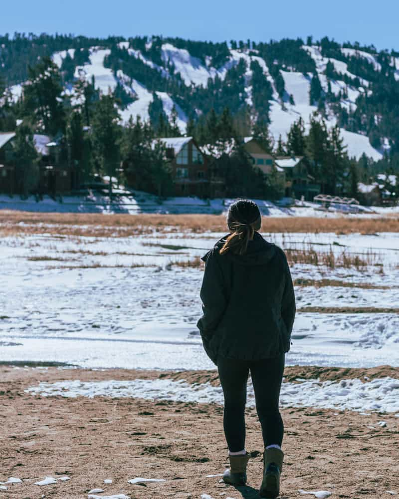 A woman dressed in black with snow boots and a ponytail with her back turned to camera looking at snowy landscape in Big Bear