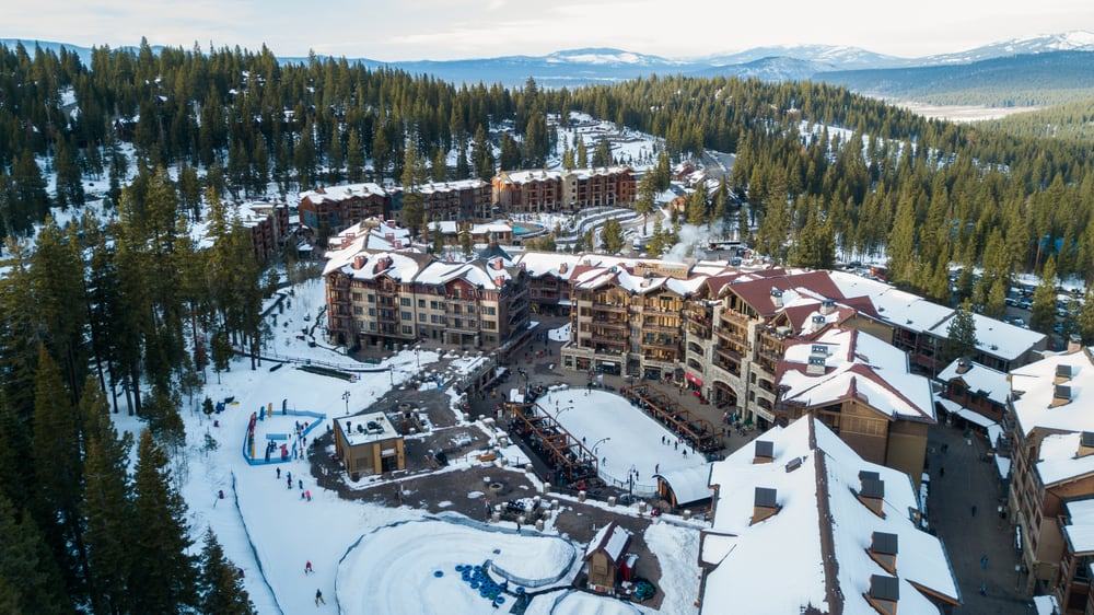 Aerial drone photo over Northstar Resort in lake Tahoe covered in snow with pine trees surrounding the facilities.