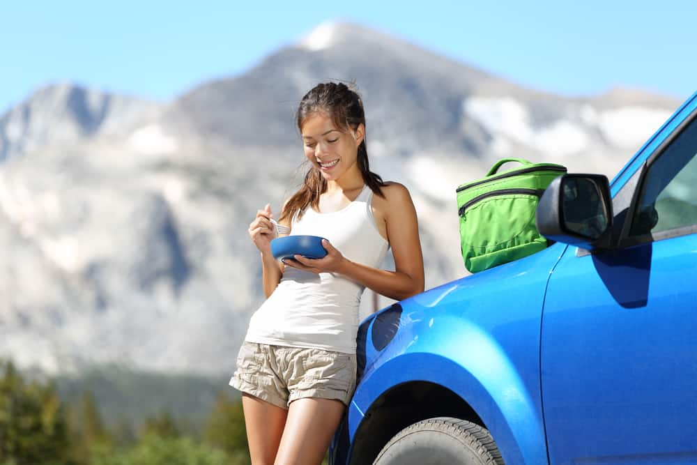 Fair-skinned woman with brown hair eating lunch from a blue bowl with a green lunch bag next to her blue car with Yosemite mountains in background