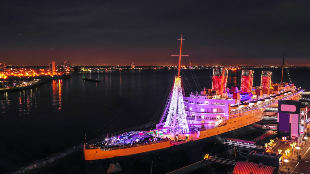 A lit-up boat with red and pink lights, the RMS Queen Mary in Long Beach California: a California Christmas hot spot
