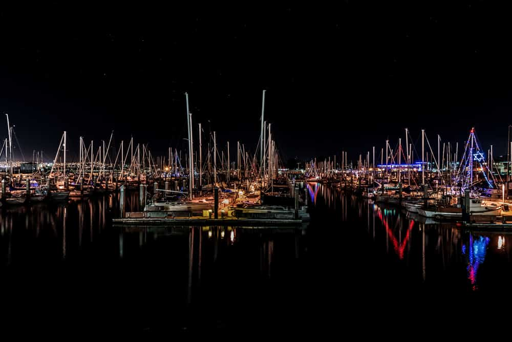 Boats and sailboats in the harbor at night with all sorts of Christmas lights reflecting in calm water.