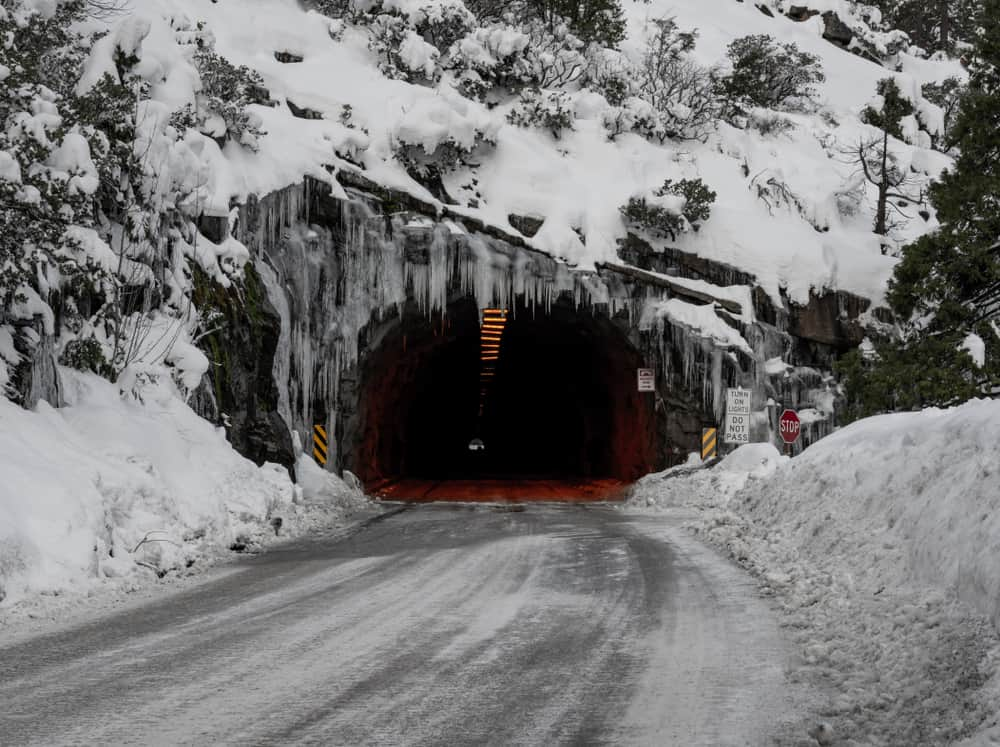 Famous Wawona tunnel with snow on sides of road with tons of snow on mountain and icicles on the opening of the tunnel.