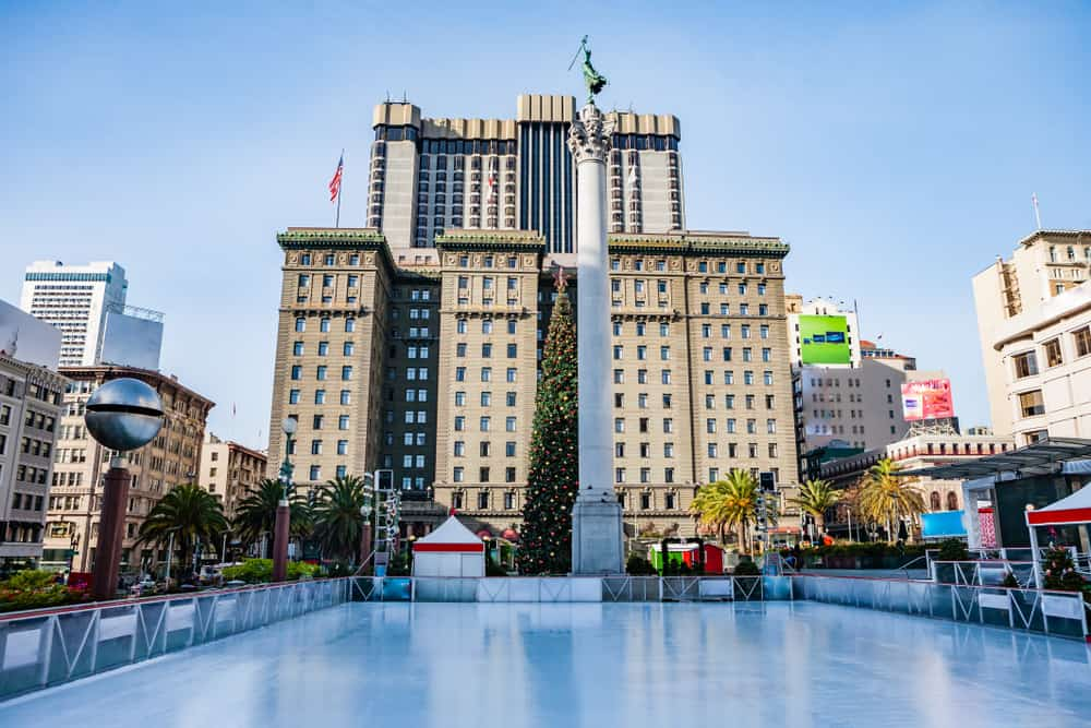 An ice rink with no one on it, with a Christmas tree and large buildings in Union Square San francisco