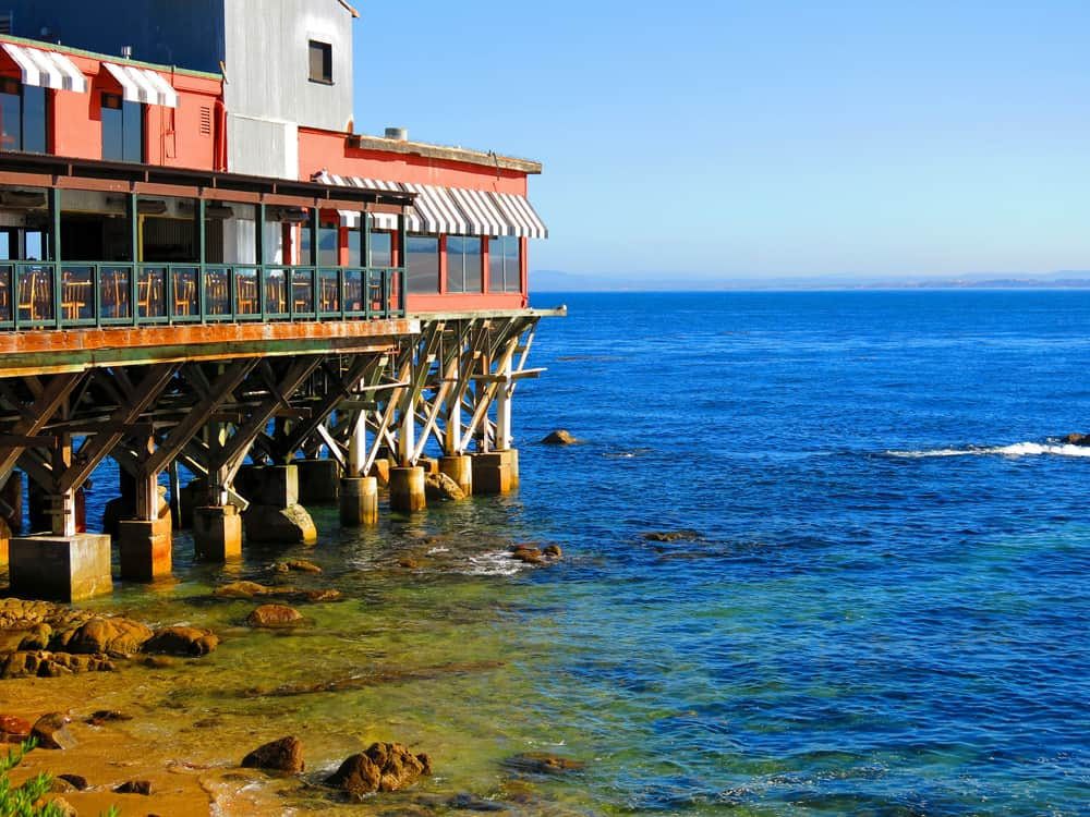 Restaurants on the water's edge in Monterey Bay: pier leading to blue sea