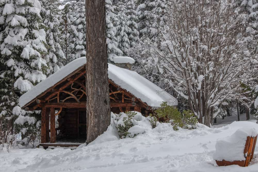 A historic wooden structure at Tallac Historic Site covered in snow with path from hikers.