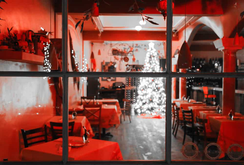 Looking through the window at a holiday-decorated restaurant in Carmel with a white lit-up Christmas tree and red interior lighting.