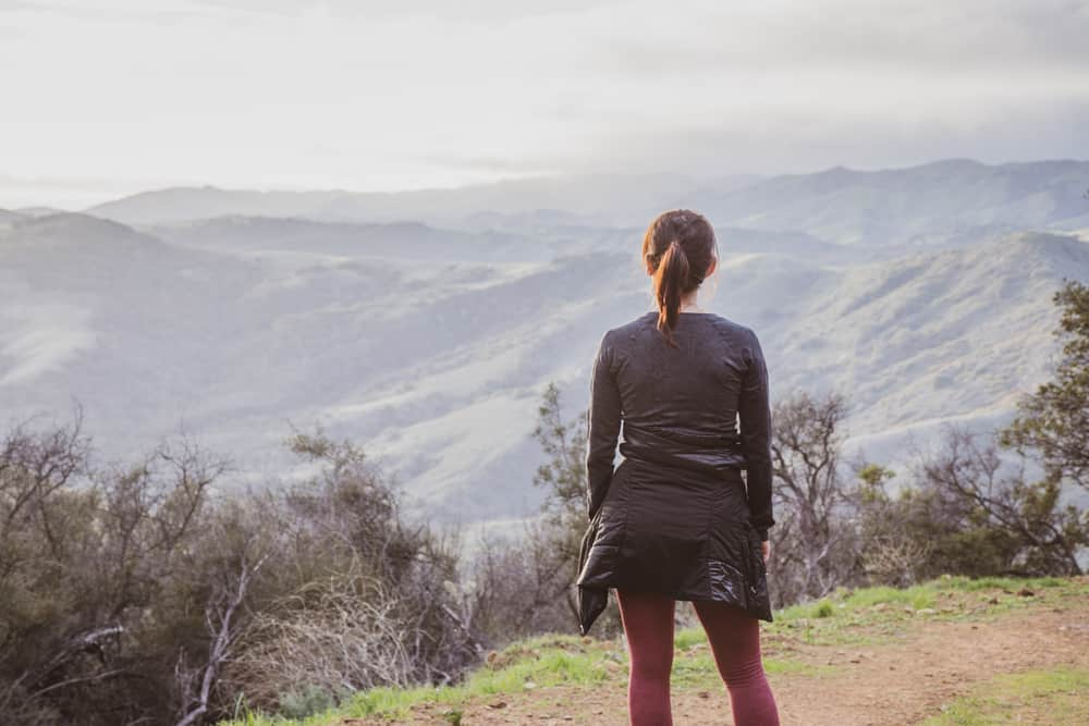 Woman with brown hair in ponytail hiking in Santa Barbara, with her back turned to camera, wearing a gray shirt and pink leggings, looking out onto rolling hills from a high elevation.
