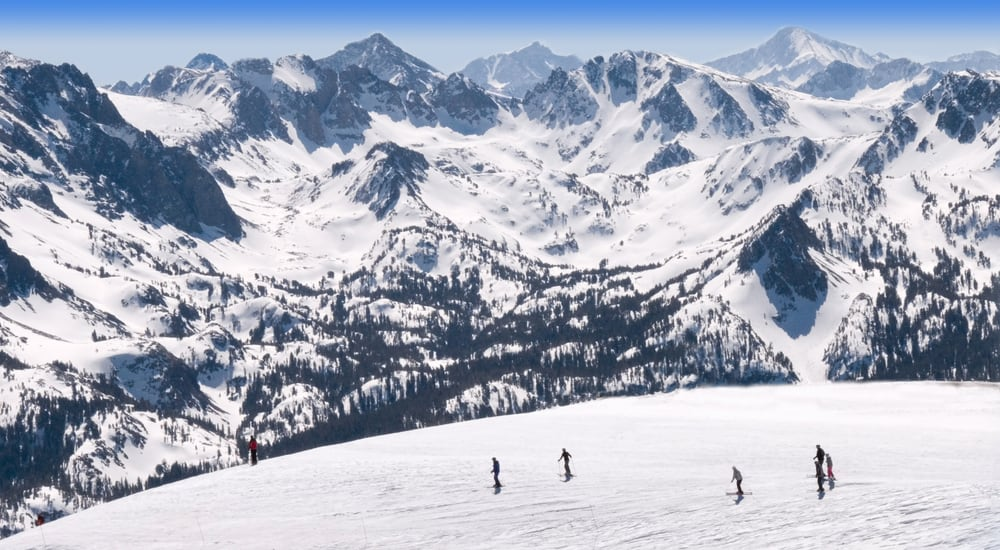 Skiers enjoying Mammoth Mountain in winter with views of Sierra Mountains in background on a sunny blue sky day.