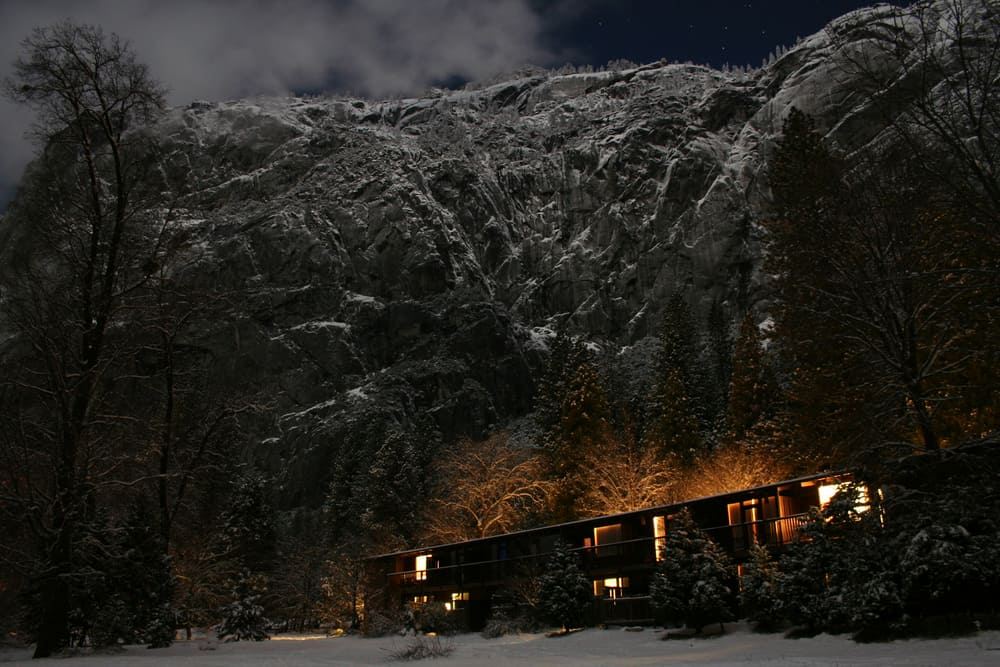 Lodge lit up with an orange glow against towering granite cliffs covered in snow in dark.