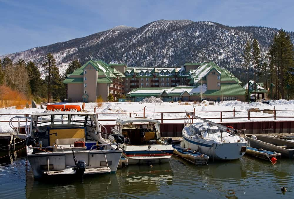 A few boats on Lake Tahoe in winter in front of a resort with a mountain in the background with snow.