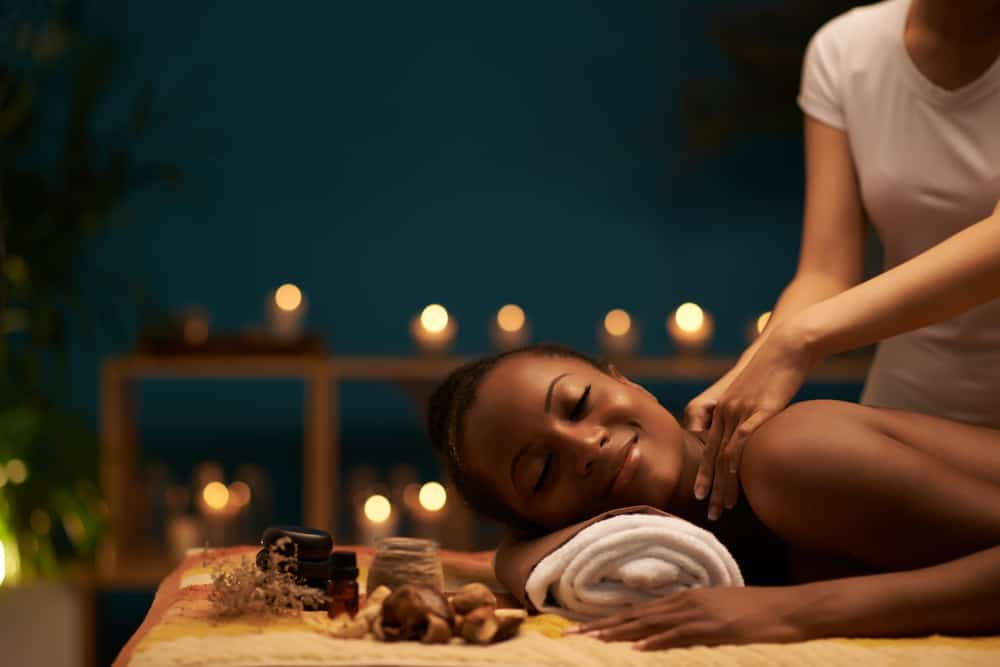 A Black woman receiving a massaging with a relaxed look on her face with candles lit in background