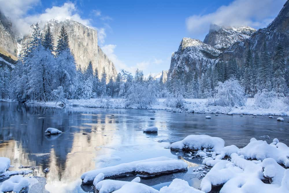 Snow on rocks in the foreground of Yosemite Valley with Merced River and views of snow-covered trees and granite rockforms with snow.