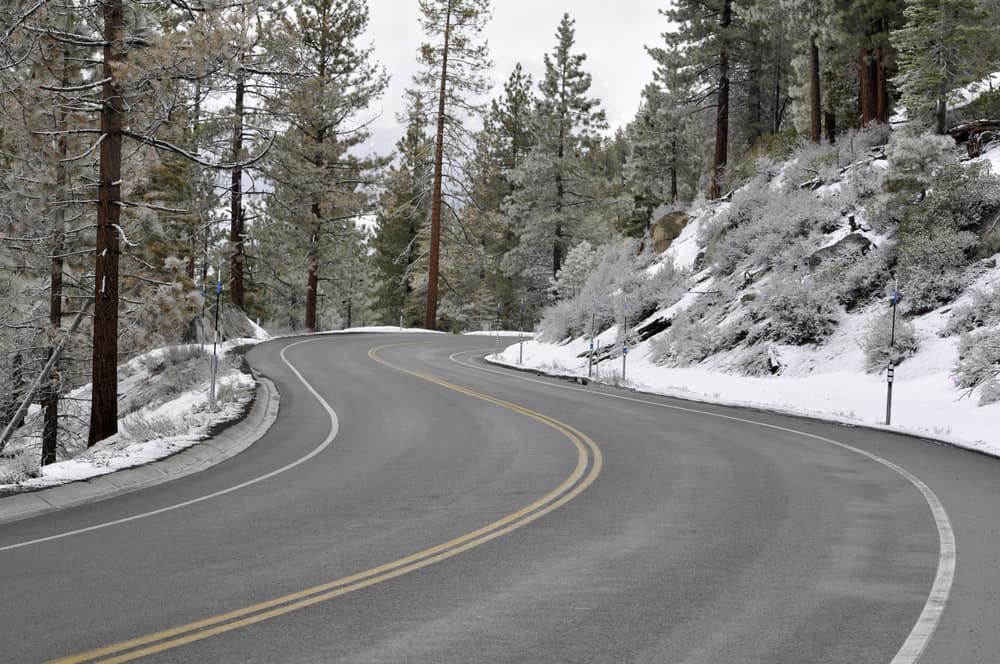 A snow-plowed winding road which leads to Lake Tahoe with snow on the sides of the road