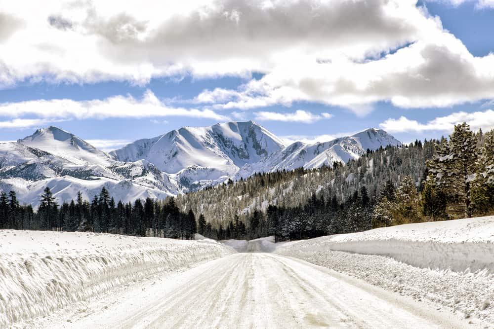 Plowed highway with snow banks on either side on a hill leading towards focal point of Mammoth Mountain and other mountains.