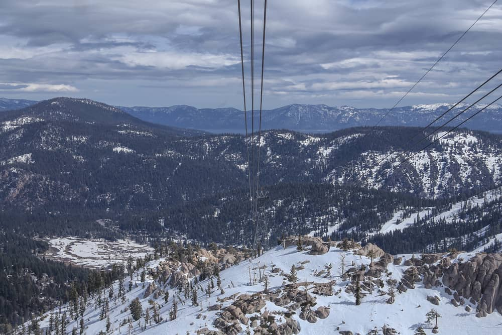 A view of the Lake Tahoe area taken from the Squaw Valley Aerial Tram with white snow, mountains, cables from the gondola, and cloudy sky.