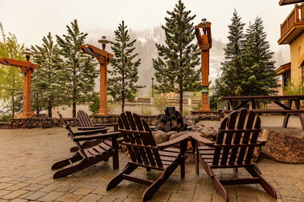 Adirondack wooden chairs assembled around a fire pit in Olympic Village on a dreary day with some snow in the forecast.