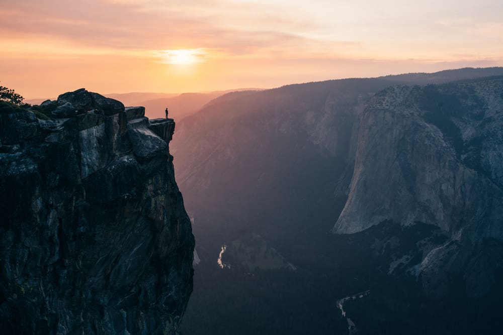 One lone figure standing on a jutting cliff edge that is a famous Yosemite viewpoint with the setting sun in the background.