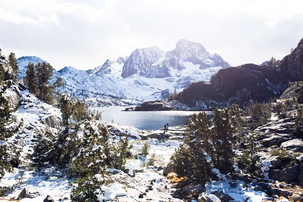 Banner Peak over Garnet Lake in the Ansel Adams wilderness after a fresh snow, everything covered in snow and white with cloudy sky.