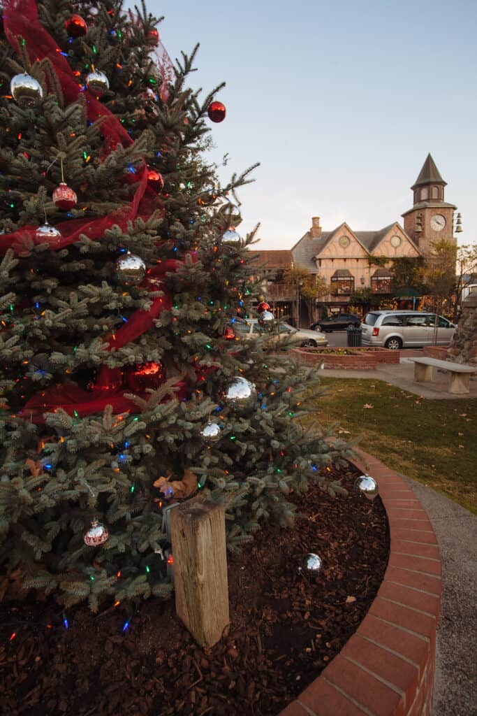 Close up of Christmas tree with European-looking village behind it in Solvang California at Christmas time