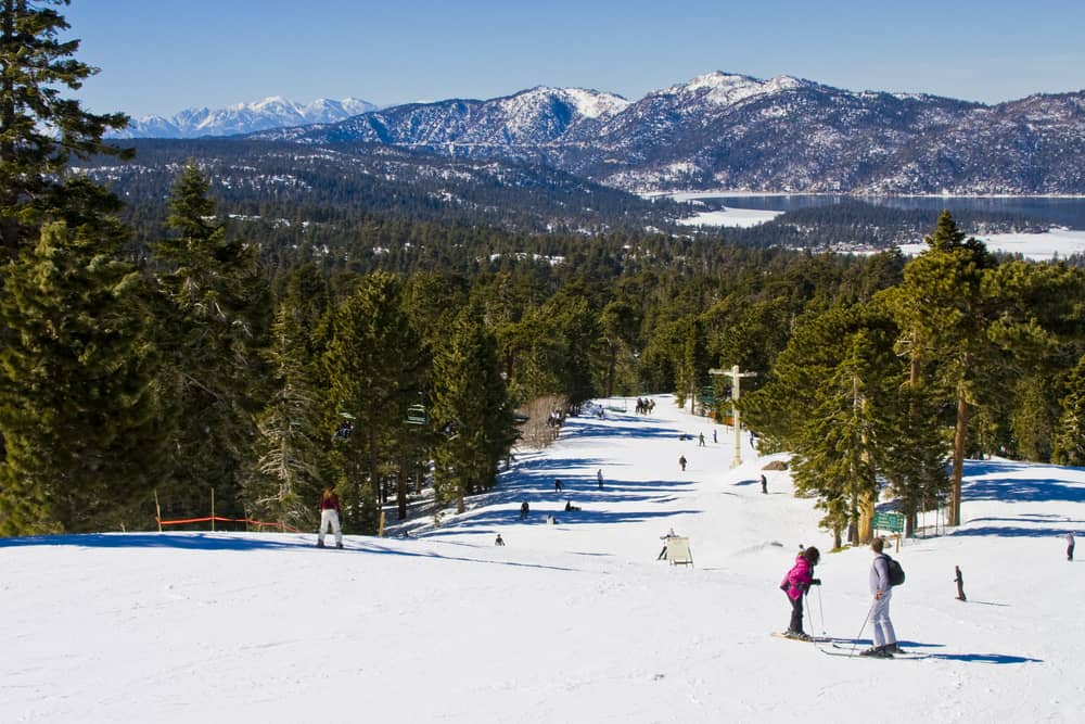 Two people talking on a downhill ski area with Big Bear Lake in background with winter scenery
