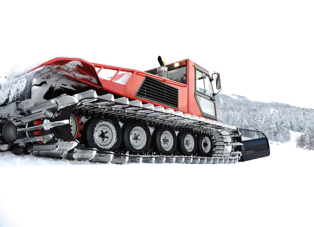 Red sno-cat vehicle meant for driving through heavy snow with chains on tires from low angle, rear view.