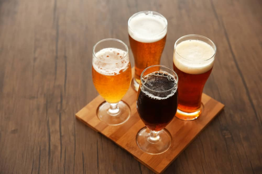 Four different kinds of beer in different colors arranged in a square on a tasting flight block of wood.