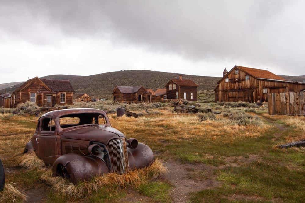 A ghost town surrounded by dilapidated homes long forgotten and a rusted car, the nature reclaiming the ghost town.