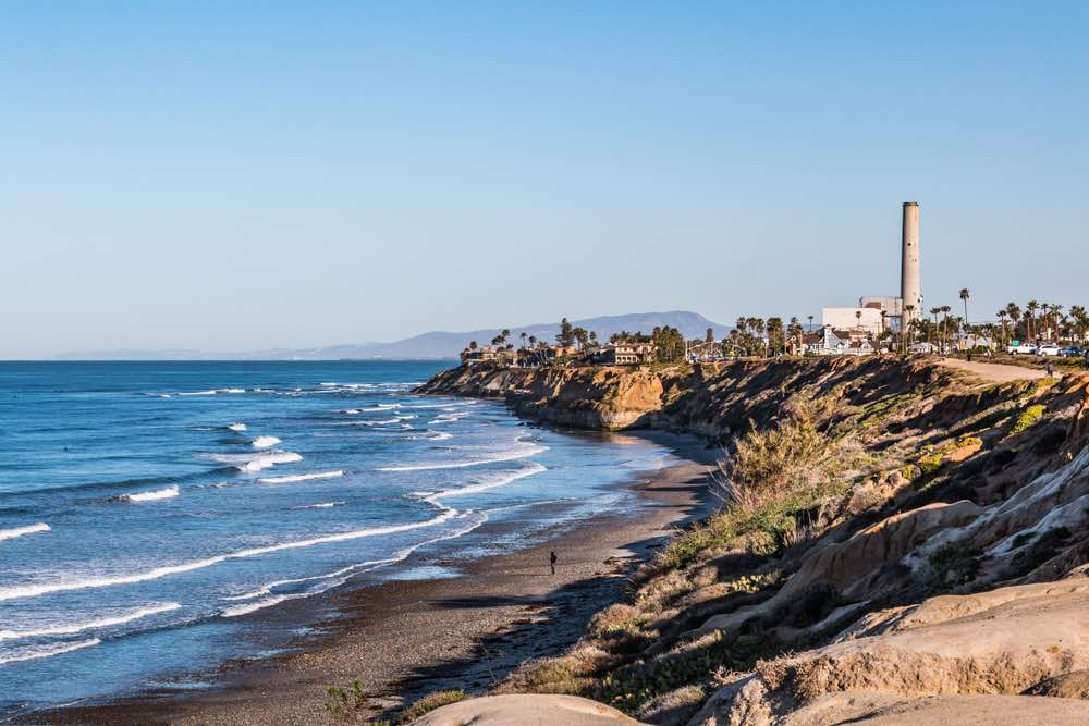 Cliffs of the Carlsbad bluffs, a beach with waves lapping onto the shore, blue sky and tall palm trees and buildings in the background.