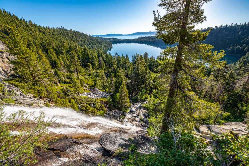 Waterfall cascading down a hill in Lake Tahoe, with a view of the glassy still Emerald Bay in the distance and Lake Tahoe further away, with tons of pine trees around.
