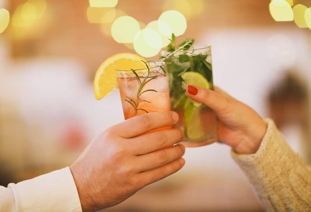 Male and female hand cheering their drink: one a pink drink with grapefruit, the other a mojito drink with mint and lime.