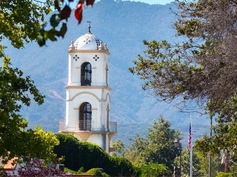 A church steeple with a background of mountains and trees and an American flag in the town of Ojai, a popular day trip from Santa Barbara