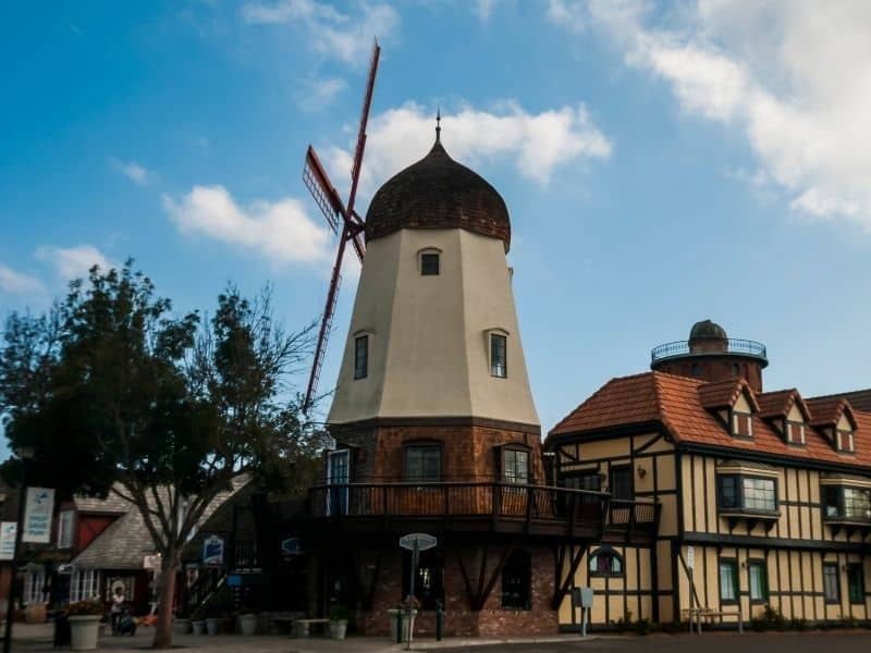 A side-angle view of Solvang's famous windmill, as well as Danish half-timber style architecture in beige and brown.