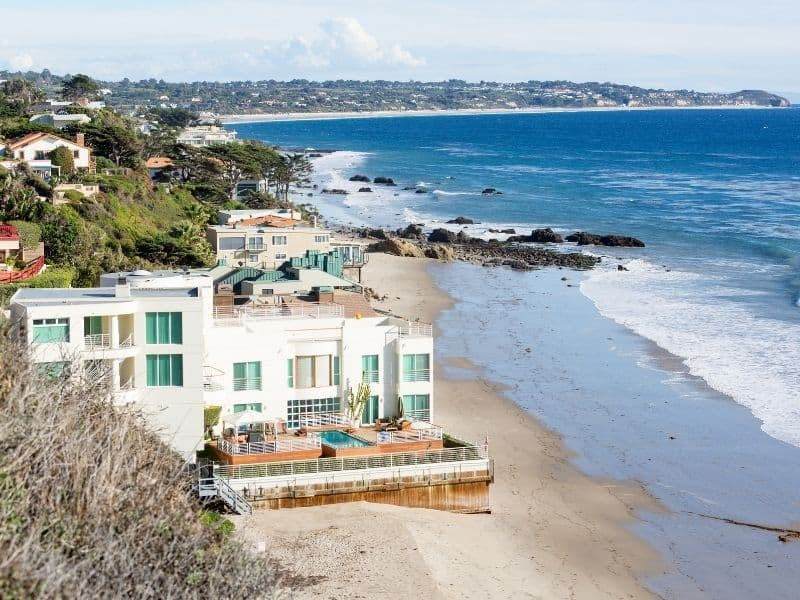 A view at a pricy Malibu home right on the beach with gorgeous ocean coastline everywhere around it.