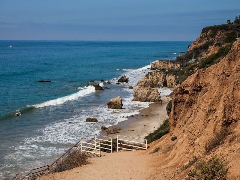 A staircase leading down to the famous El Matador beach in Malibu. Orange cliffs leading to the Pacific Ocean with a small beach with lots of rock formations.