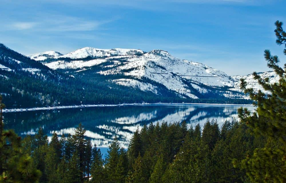 Snow-covered Donner Peak reflecting in the glassy still Donner Lake below on this popular Donner Lake hike near Tahoe.