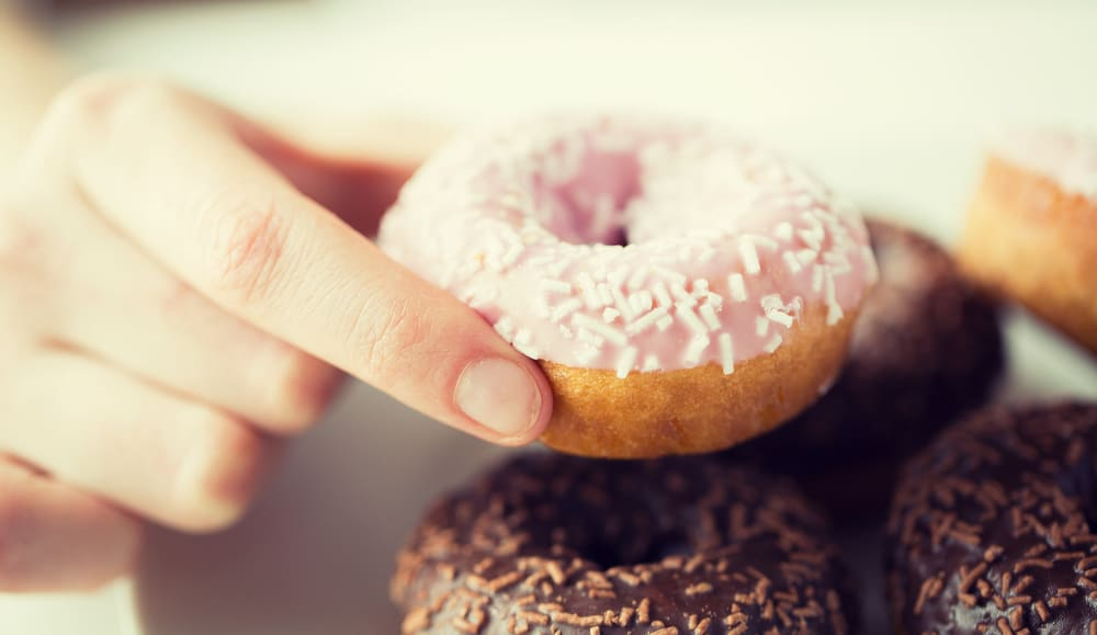 Hand holding a donut with strawberry frosting with white sprinkles and chocolate frosted donuts below it.