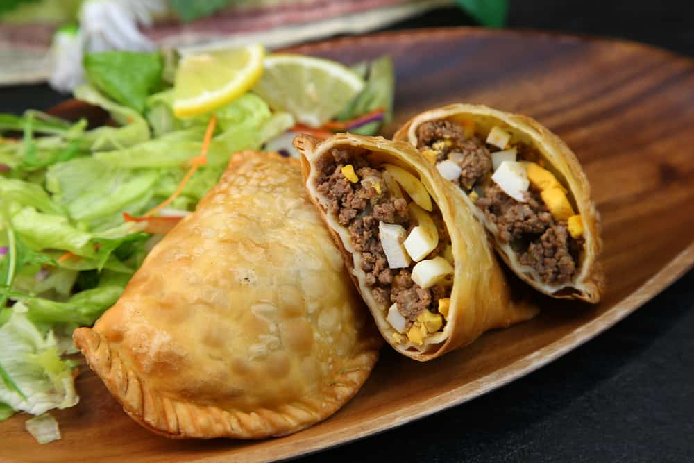 Empanadas (wheat pastries stuffed with filling) with beef and hard boiled egg served with salad.