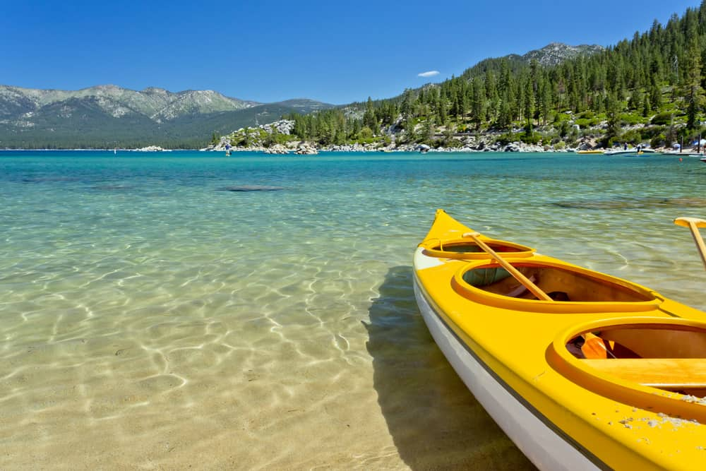 A yellow kayak contrasting with the turquoise blue waters of Lake Tahoe which are crystal clear near the beach edge