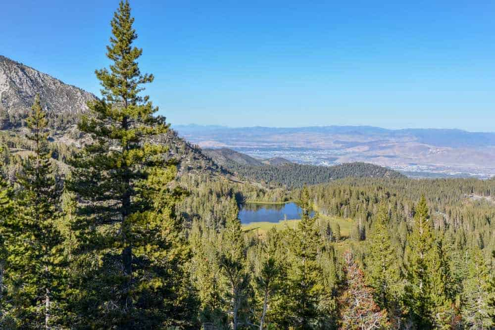 View of Tamarack Lake as seen from the Tahoe Rim Trail with lots of pines and smaller mountains and Reno Valley off in the distance.
