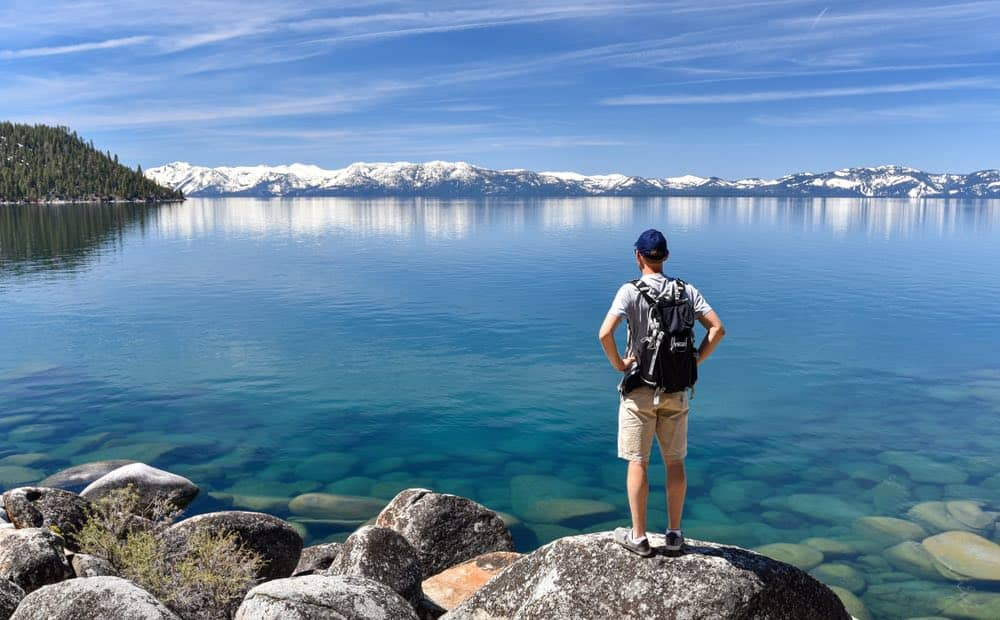 Caucasian man hiking in Lake Tahoe during the summer, looking at the turquoise water and seeing snow-covered mountains in the distance.