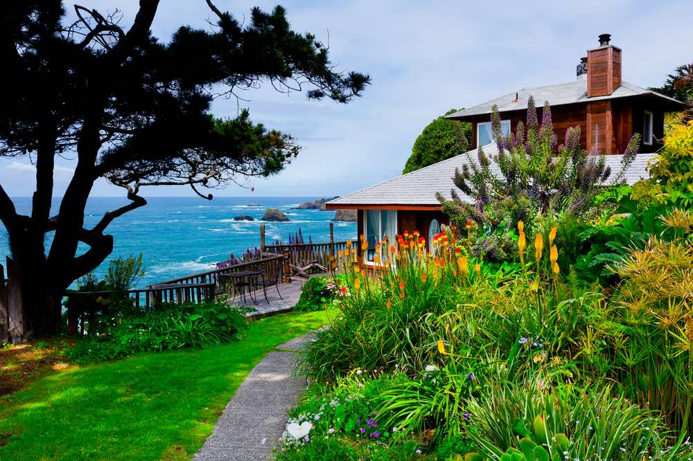 A picturesque cabin house in Mendocino with birds of paradise orange flowers overlooking a cliff with blue ocean beneath it