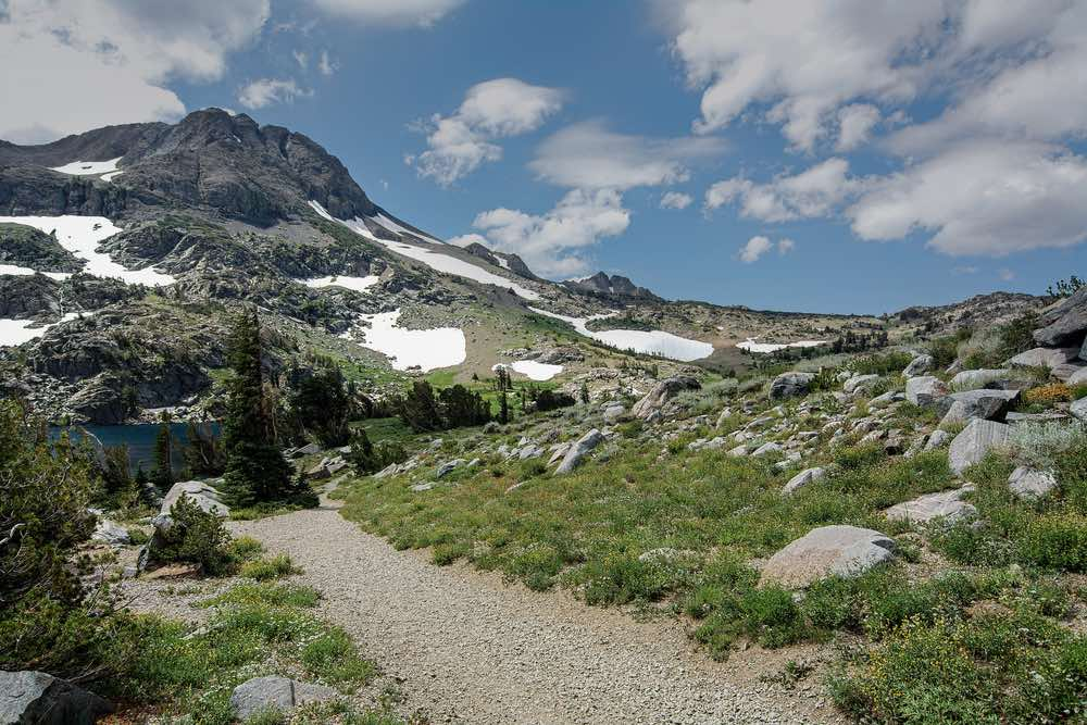 A gravely hiking path leading from a lake, the path connects Winnemuca Lake above with Frog Lake and other destinations along the Pacific Crest Trail. View of clouds in the sky, melting snowpack, and grassy trail.