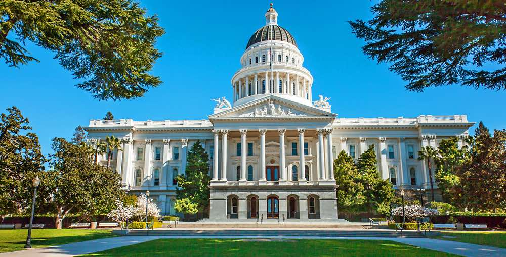 White Capitol government building with a green lawn surrounded by trees at the California state capital