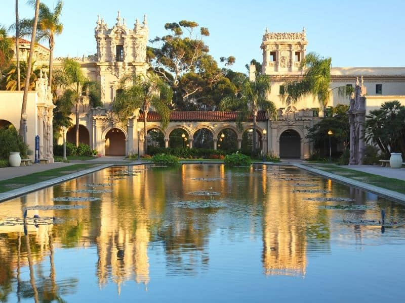 View of the pond at Balboa Park, reflecting a Spanish-colonial architecture building and lots of trees and palm trees
