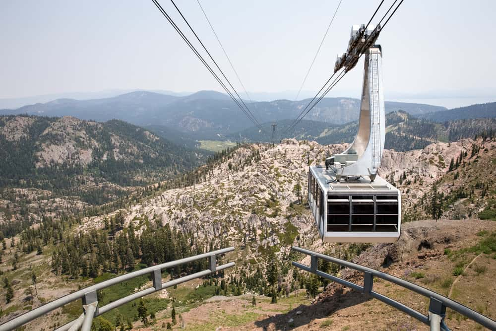 Aerial tramway car hoving over an alpine landscape of rocks, mountains, and pine trees.