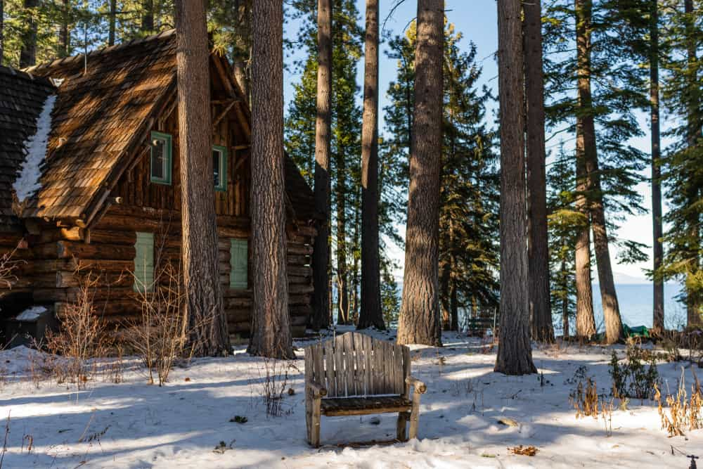 Old wood cabin with a wooden chair in the center of the photo next to a lake with some light snow on the ground.