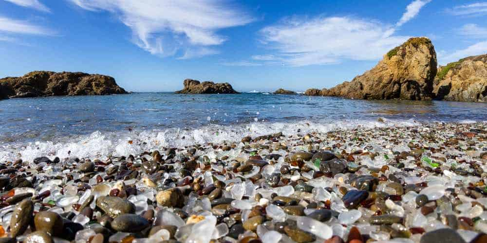 The pebbles of the Glass Beach at Fort Bragg, low angle with glass detail and water coming in as tide