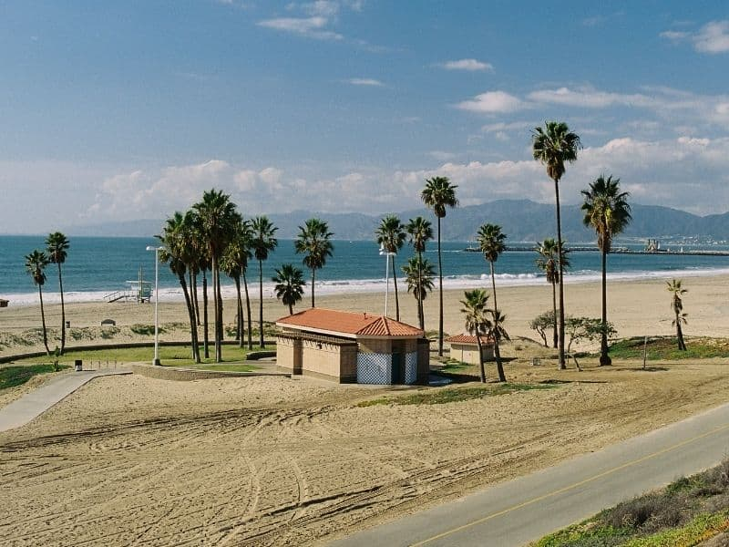 Bike path on a partly cloudy day in Los Angeles by the beach with blue ocean and lots of palm trees: riding a bike on The Strand is one of the best outdoor things to do in Los Angeles!
